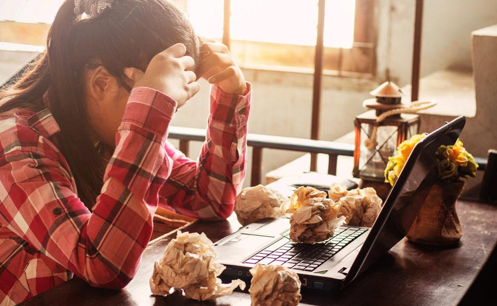 Mujer-con-nervios-por-estudiar-examenes-en-la-mesa