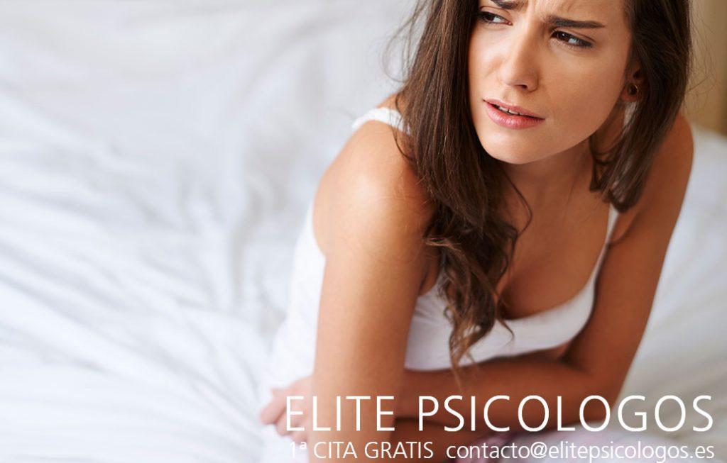 Mujer en la cama con dolor de estómago crónico