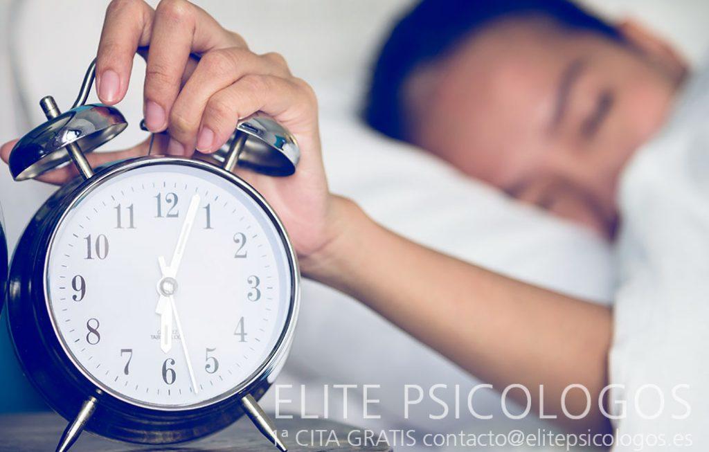 Mujer posponiendo la alarma porque está muy cansada