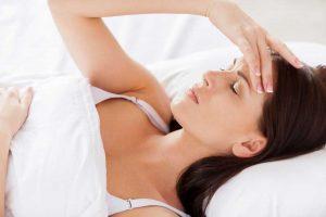 Insomnio. Atractiva mujer joven cogiendo la mano en el cabello y manteniendo los ojos cerrados mientras está acostada en la cama